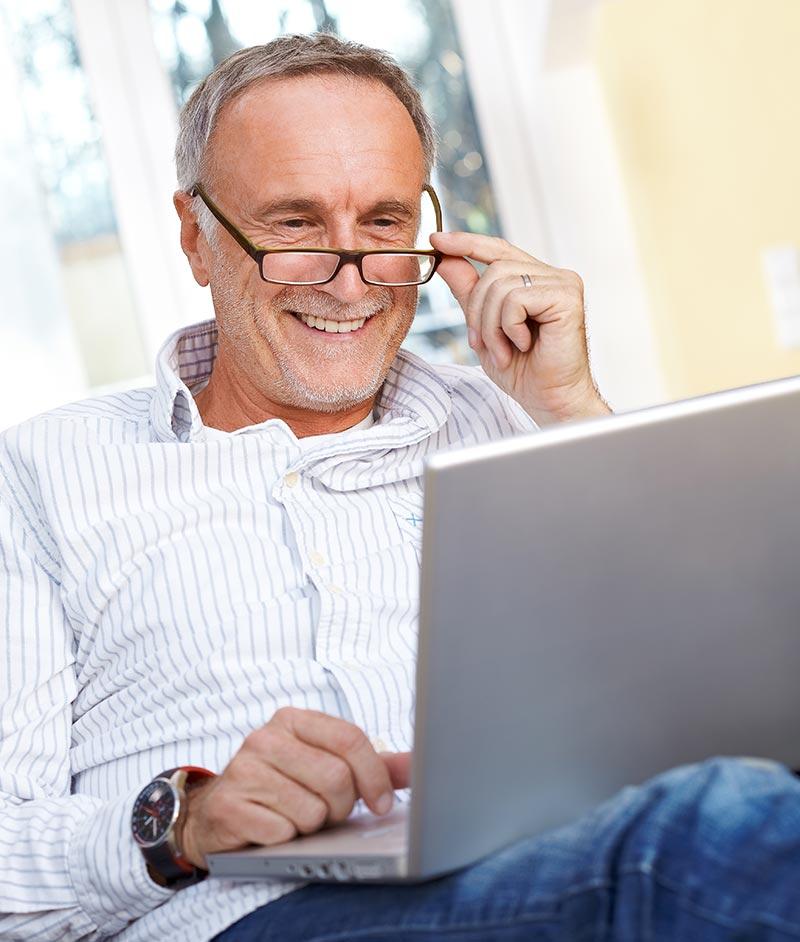 Senior man with glasses using laptop