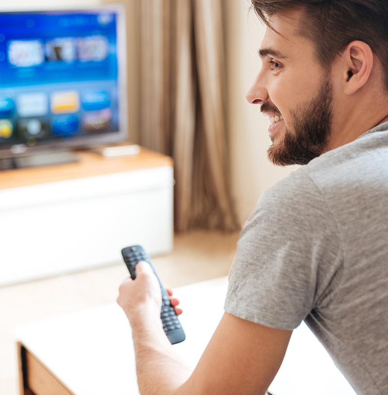 Profile of man with beard using a TV remote